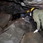 Folk der kravler rundt på lavabrokker i grotten
